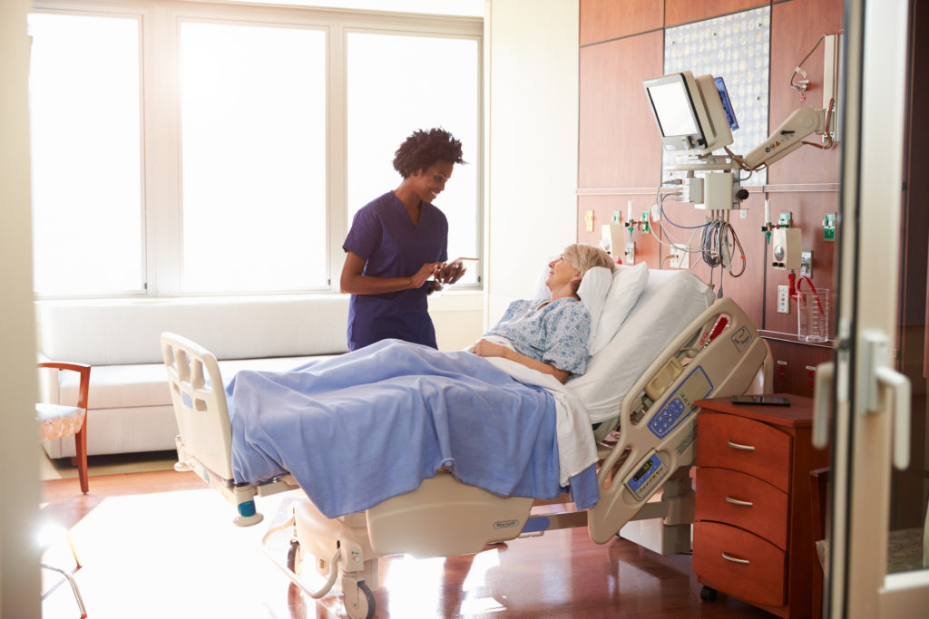 Nurse holding a tablet and speaking with middle aged female patient lying in a hospital bed.